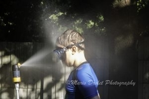 Boy with goggles facing a water sprinkler