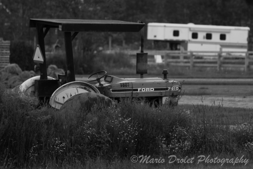 Black and white photo of an old tractor abandoned in a field