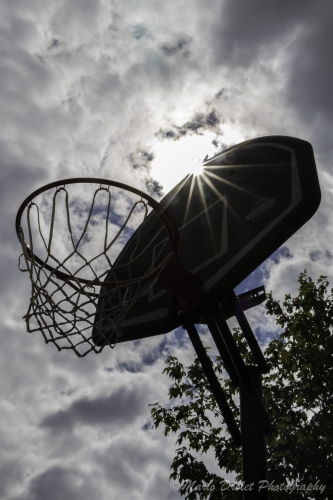 Colour photo of a sunflare behind a basketball net backboard