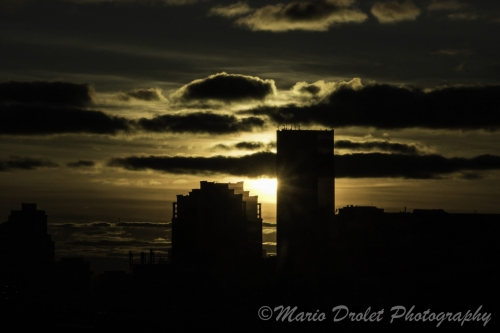 Colour photo of a sunset behind city buildings