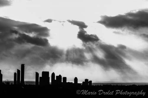 High contrast overexposed black and white photo of buildings under a cloudy sky
