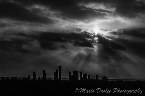 High contrast black and white photo of buildings under a cloudy sky