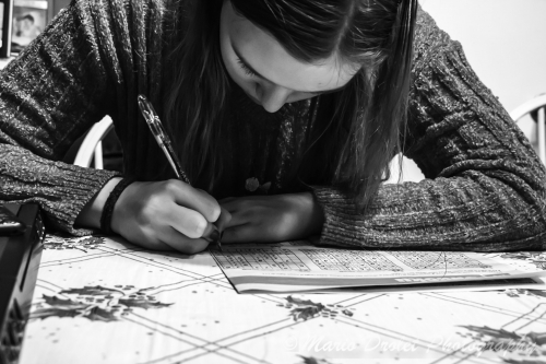 Black and White photo of someone doing sudoku puzzles