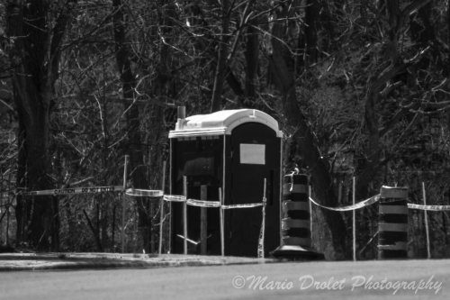 Port-a-potty on the side of the road in black and white
